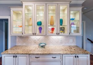 Glass kitchen cabinets from Houston glass company with multi-colored vases displayed inside