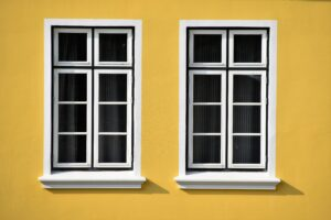 two Houston residential glass windows against yellow wall